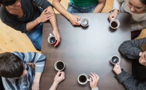 People gathered around a table and drinking coffee