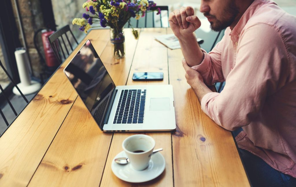 Man enjoying a cup of coffee in the morning with his laptop
