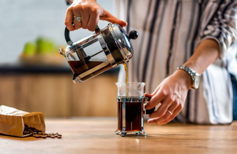 Man pouring freshly made French press coffee into a cup