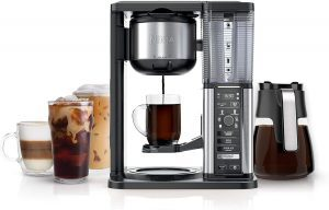 Ninja Special Coffee Maker with a glass carafe, brewing coffee into a glass mug with specialty coffee drinks on the side