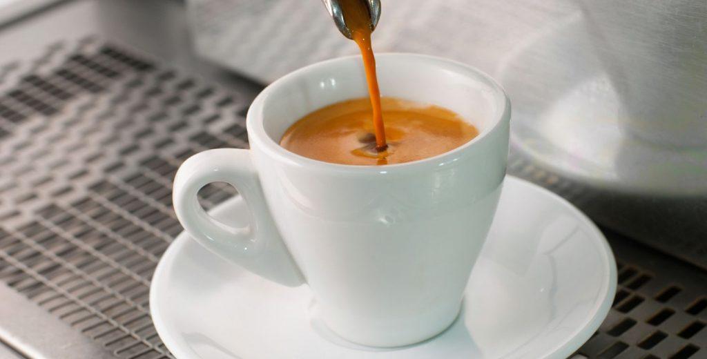 Espresso pouring from a professional espresso maker into a white cup