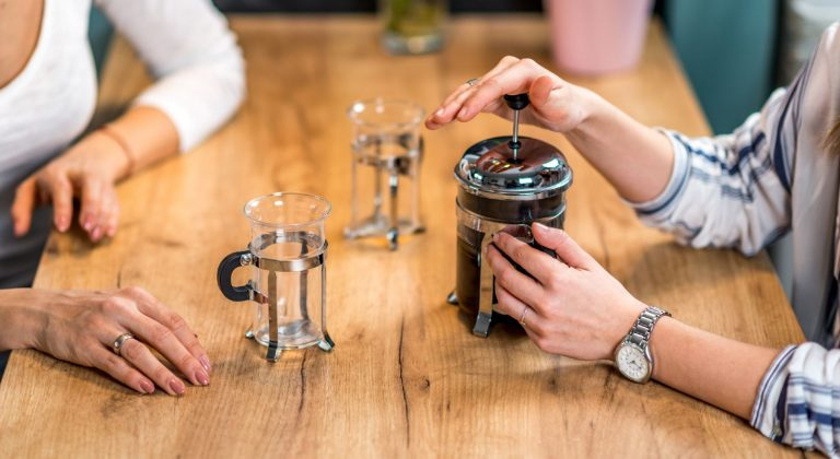 Women making French press coffee and serving it in two cups on a wooden dining table