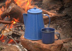 Blue percolator at a camp fire served in a blue metal mug