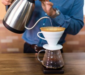 Making pour-over coffee with a gooseneck kettle and a ceramic filter basket