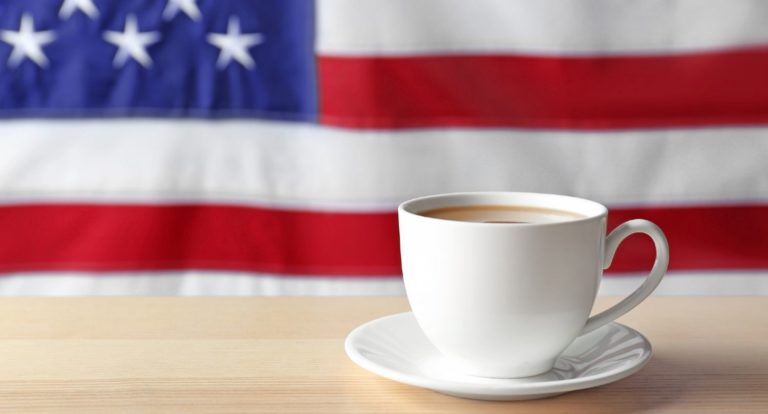 Cup of coffee on a wooden table with the American flag in the background